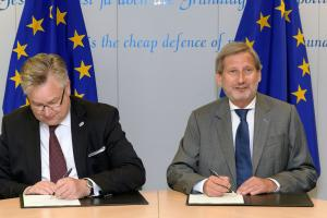 The Director of OSCE Office for Democratic Institutions and Human Rights (ODIHR) Michael Georg Link (l) and EU Commissioner for European Neighbourhood Policy and Enlargement Negotiations Johannes Hahn (r) sign an agreement launching a new project to support democratic elections in the Western Balkans in Brussels, 27 June 2017. (EC - Audiovisual Service/Georges Boulougouris)
