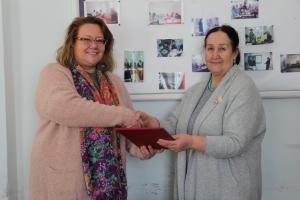 Туула Юрьёля, Глава Бюро ОБСЕ в Таджикистане (слева) и Муазама Усманова, Директор НПО «Оксана» (справа), подписывают новое соглашение об осуществлении проектов, район Балхи, Хатлонская область, 3 марта 2017 года.   (ОБСЕ/Мунира Шоинбекова)