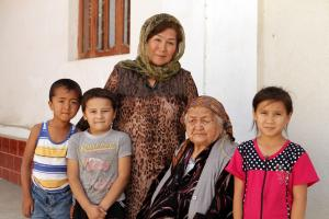 Mavlyuda Kasymova, leader of a Women's Initiative Group in Osh, with her family, 17 September 2014. (OSCE/Jonathan Perfect)
