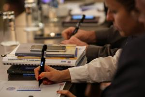 Participants in the 2018 Human Dimension Implementation Meeting test digital pens used by ODIHR election observers at an interactive side event. Warsaw, 11 September 2018. (OSCE/Maria Kuchma)