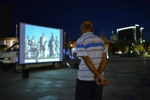 "Festival attendee, watching a screening of the Polish film ""Defilada – The Parade"" at the Scanderbeg Square, Tirana, 18 September, 2017. (Ardit Muhaxhiri)"