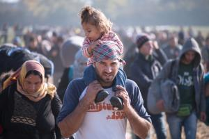 Refugee baby on father's shoulders (iStock/Milos Malinic)