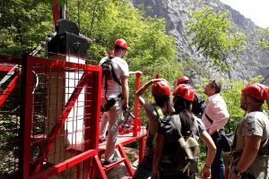 Participants of the activity promoting inter-community dialogue and inter-municipal co-operation line-up to ride the Zip Line, Rugova valley, 24 June 2019  (OSCE/Riccardo Celeghini)