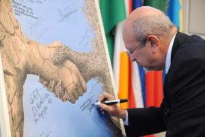 OSCE Secretary General Lamberto Zannier signing the poster with the winning design of the joint OSCE-eYeka crowdsourcing competition on security and climate change, during the OSCE Security Days event on climate change and security, Vienna, 28 October 2015.   (OSCE/Micky Kroell)