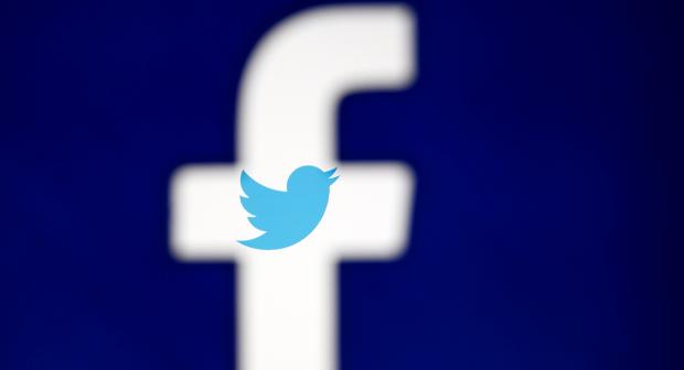 A 3D-printed Facebook logo is displayed in front of the Twitter logo, in this illustration taken October 25, 2017.  (REUTERS/Dado Ruvic/Illustration)