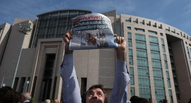A press freedom activist holds a copy of the newspaper Cumhuriyet during a demonstration in solidarity with the jailed members of the newspaper Cumhuriyet outside the courthouse, in Istanbul, Turkey, September 25, 2017.  (REUTERS/Osman O)